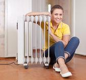 Smiling woman near warm radiator — Stock Photo