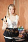 Female visagiste with cosmetics — Stock Photo