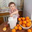 Baby girl making fresh orange juice — Stock Photo