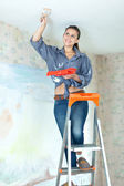 Woman paints ceiling with brush — Stock Photo