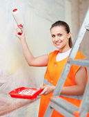 Painter paints wall with roller — Stock Photo