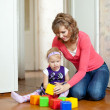 Stock Photo: Mother plays with baby in home