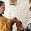 Priest at Sretenskaya church performing christening ceremony - Stock Photo