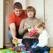 Parents and child plays with meccano set — Stock Photo