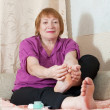 Woman looks at her toenails — Stock Photo