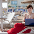 Woman using laptop at beach — Stock Photo
