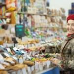 Mature woman chooses sweets — Stock Photo