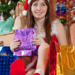 Girl sits with christmas gifts - Stockfoto