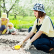 Women with child works at garden — Stock Photo #18198797