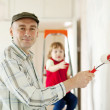 Father with child paints wall — Stock Photo #18198955