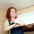 Woman glues ceiling tile at home — Stock Photo #18199071