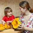 Happy mother with girl cooks pumpkin — Stock Photo #18199447