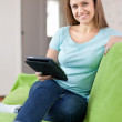 Girl with e-book on sofa — Stock Photo #18199751