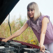 Woman looking under the car hood - Stock Photo