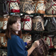 Young woman chooses bag - Foto Stock