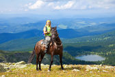 Female rider at mountains peak — Stockfoto