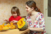 Mother with daughter cooking pumpkin at kitchen — Stock Photo