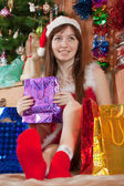 Girl sits with christmas gifts — Stock Photo