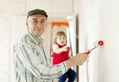 Father with child paints wall — Stock Photo
