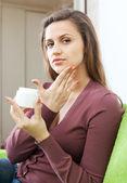 Beautiful woman puts cream on face — Stock Photo