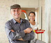 Happy man and woman paints wall at home — Stock Photo