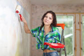 Happy woman paints wall — Stock Photo