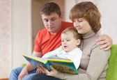 Ouders met kind kijkt het boek — Stockfoto