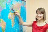 Woman showing something on world map — Stock Photo