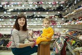 Woman with child chooses baby shoes — Stok fotoğraf