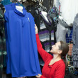 Mature woman  chooses clothes - Stok fotoğraf