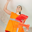 Female house painter paints the ceiling - Stock Photo