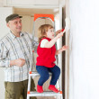 Father with child paints wall - Stock Photo