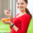 Young woman in red eats grapefruit — Stock Photo