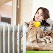 Woman near oil heater at home — Stock Photo
