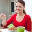 Stock Photo: Happy girl eats buckwheat at home