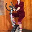Stock Photo: Womworking out on exercycle