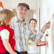 Parents with child paints wall at home — Stock Photo