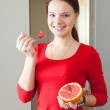 Girl in red eats grapefruit — Stock Photo