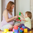 Stock Photo: Pregnant mother plays with child