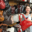 Woman chooses leather bag at shop — Stock Photo