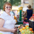 Stock Photo: Mature womchooses fruits