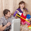 Family at home near oil heater — Stock Photo #18202481