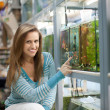 Woman chooses  fish tank — Stock Photo