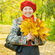 Elderly woman with maple leaves — Stock Photo