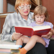 Grandmother and child reading  book together - Stock Photo