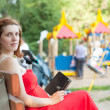 Royalty-Free Stock Photo: woman reads e-book against  playground area