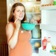 Royalty-Free Stock Photo: Pregnant woman eats from  fridge  at home