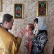 Baby being baptized at Orthodox church - Stock Photo