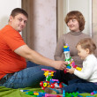 Stock Photo: Parents and child plays with meccano