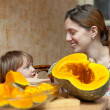 Stock Photo: Woman with child cooks pumpkin
